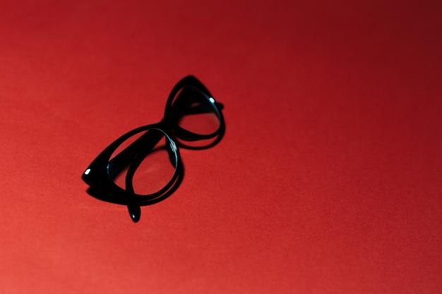 Primo piano di occhiali neri su sfondo per studio di colore rosso scuro con spazio di copia.
