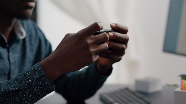 Primo piano delle mani dell'uomo di colore che giocano online ai videogiochi mobili di internet sul suo telefono a casa per il tempo libero ...