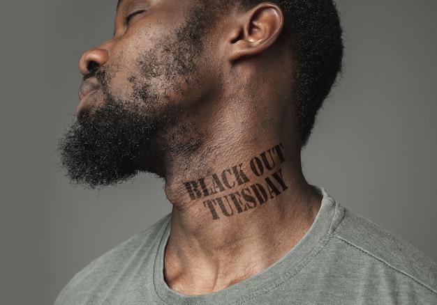 Close up uomo nero stanco della discriminazione razziale ha tatuato lo slogan black lives matter