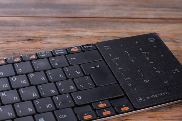 Chiuda sulla tastiera nera del pc. vecchia scrivania in legno marrone.