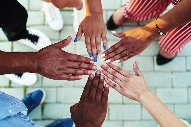 Primo piano su persone di colore con le mani unite