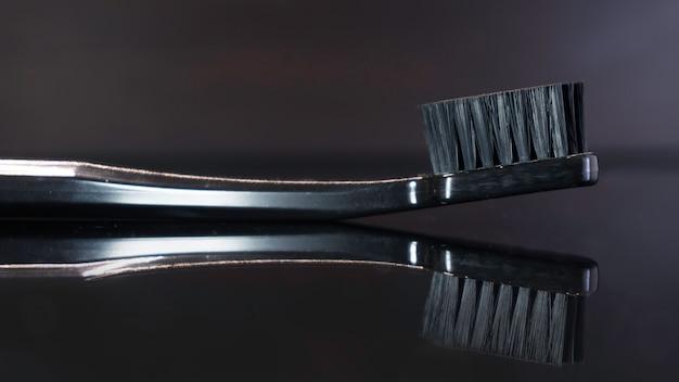 Primo piano su spazzolino da denti nero posa sulla superficie riflettente