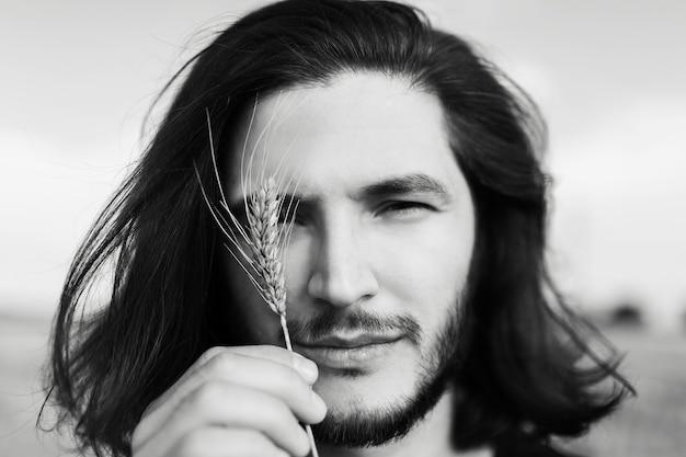 Close-up foto in bianco e nero di un bel giovane con lunghi capelli scuri.