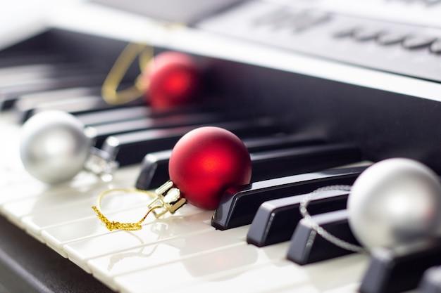 Primo piano della tastiera del pianoforte in bianco e nero con palla di natale