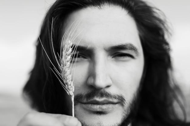 Close-up ritratto in bianco e nero di bel giovane con i capelli lunghi.