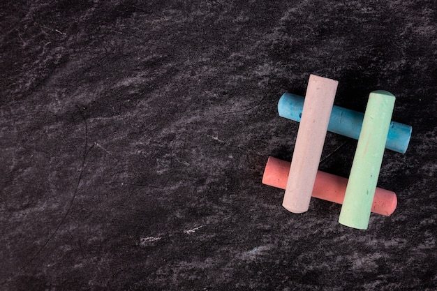 Primo piano di una lavagna con pezzi di gesso colorato disposti sotto forma di hashtag.
