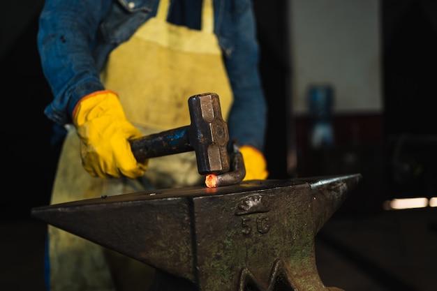 Primo piano delle mani del fabbro che lavorano con un martello su un pezzo di metallo caldo.