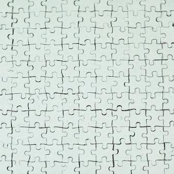 Avvicinamento. scheda vuota raccolta da pezzi di puzzle su sfondo grigio.