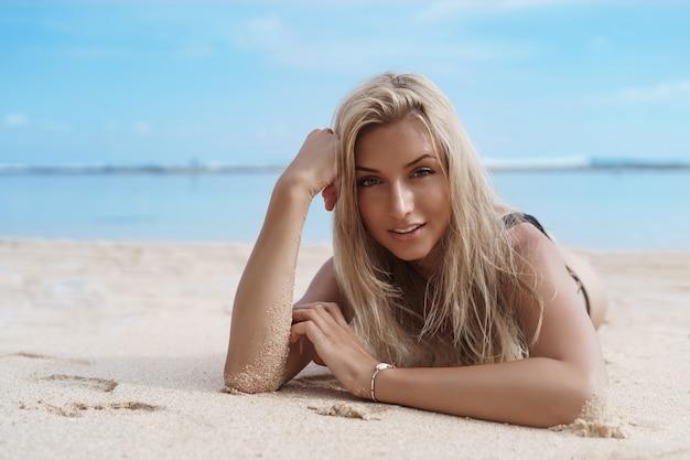 Chiuda in su della giovane donna bionda si sdraia sulla spiaggia sabbiosa.