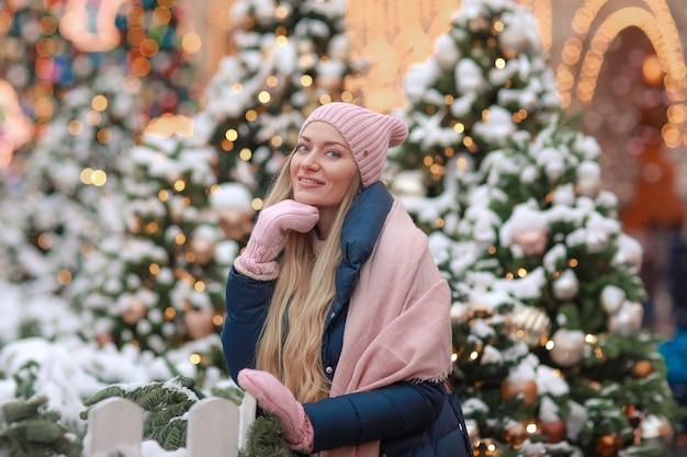 Primo piano di una bionda in guanti e una sciarpa sullo sfondo degli alberi della città di capodanno