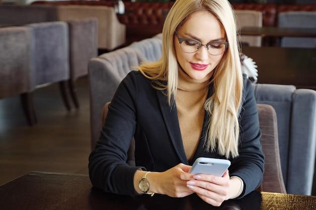 Close up donna bionda in tuta con telefono seduto a un tavolo in un bar, copia spazio