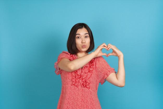 Primo piano soffiando un bacio con le labbra una giovane donna asiatica fa il simbolo del cuore dalle sue dita
