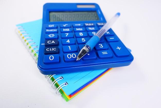 Close up blu calcolatrice e blocco note sul colore di sfondo.