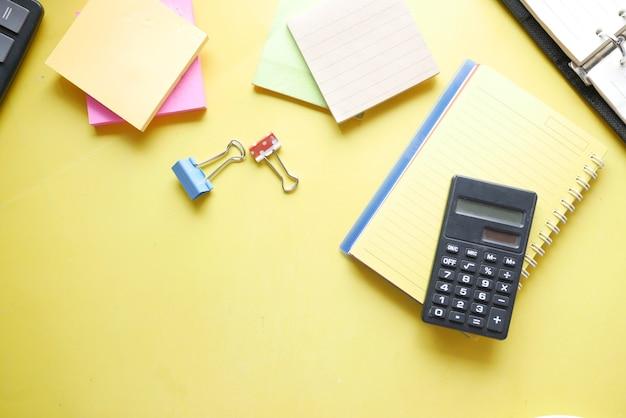 Primo piano di calcolatrice blu e blocco note su sfondo colorato color