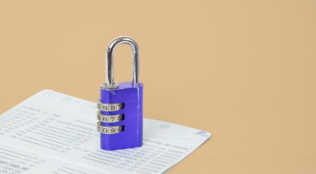 Close up chiave blu o lucchetto bloccato sul libretto di conto su sfondo bianco. concetto di risparmio e finanziario, sicurezza aziendale finanziaria o sicurezza dell'account. copia spazio.
