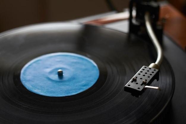 Primo piano del record di musica blu sulla piattaforma girevole, ago della piattaforma girevole che gioca musica