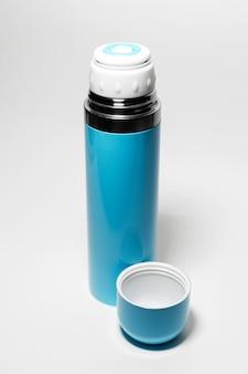 Primo piano del thermos blu su bianco
