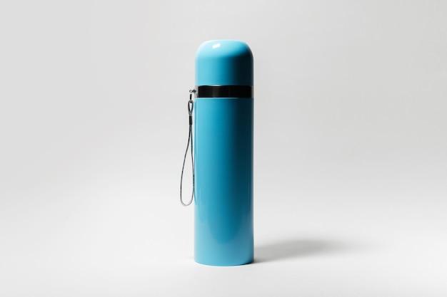 Primo piano del thermos blu su bianco.