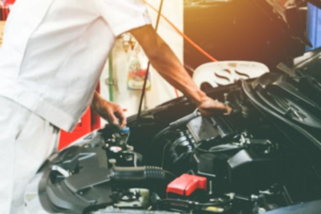 Primo piano sfocato stazione di riparazione auto e riparatore che lavora con il motore dell'auto. concetto di manutenzione..