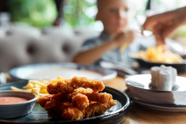 Primo piano bambino sfocato e fast food