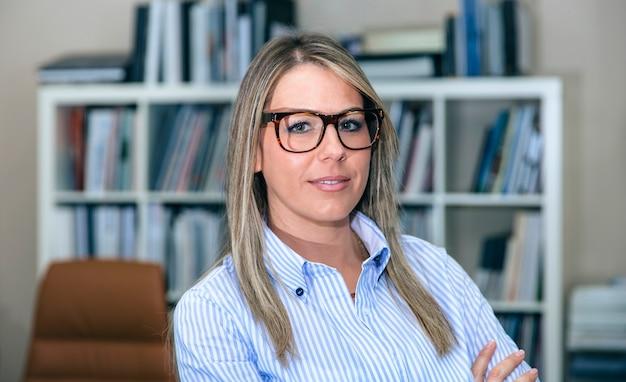 Close up bonde imprenditrice sorridente in piedi in ufficio contro della libreria