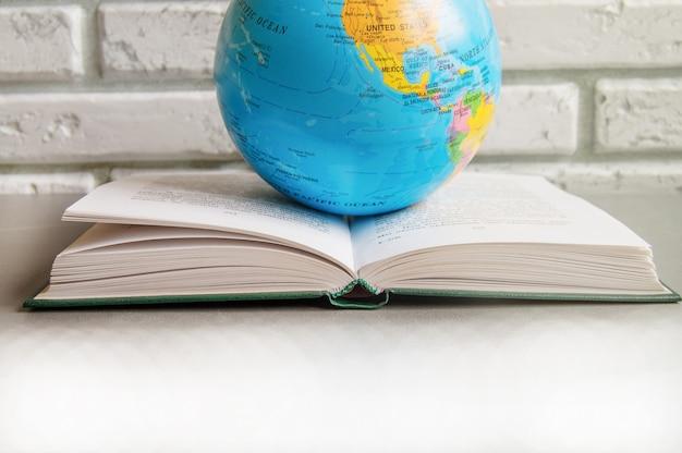 Primo piano di un libro aperto su una biblioteca libri da tavolo e un globo, contro un muro di mattoni in classe, la luce del sole, il concetto di giornata mondiale del libro
