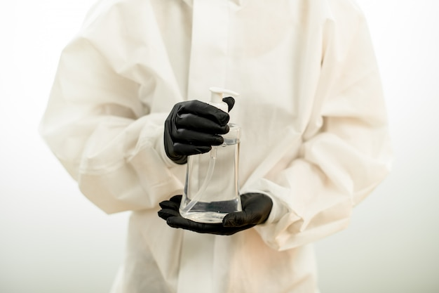 Primo piano della bottiglia con disinfettante nelle mani della persona in guanti neri e tuta protettiva bianca