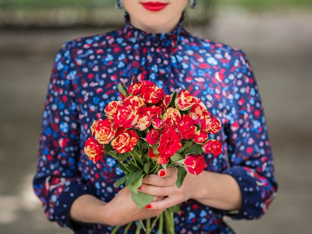 Close up di bouquet di fiori. elegante donna irriconoscibile che tiene un mazzo di rose rosse
