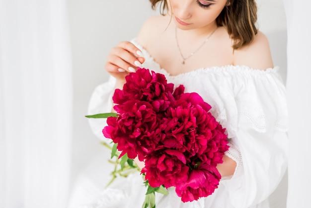 Primo piano di un mazzo di peonie nelle mani di una ragazza. ragazza in vestito bianco che tiene i fiori rossi