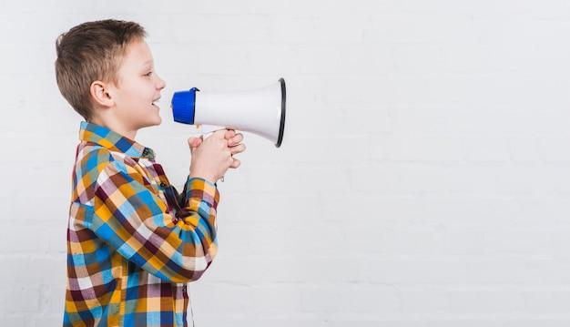 Primo piano di un ragazzo che grida fortemente in megafono contro fondo bianco