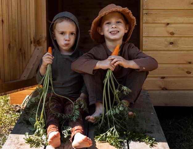 Primo piano sui ragazzi che mangiano carote vicino alla stalla