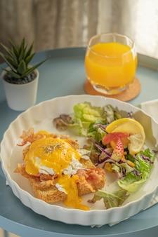 Primo piano su una colazione o un brunch, le uova alla benedict servono con pancetta fritta e pane tostato