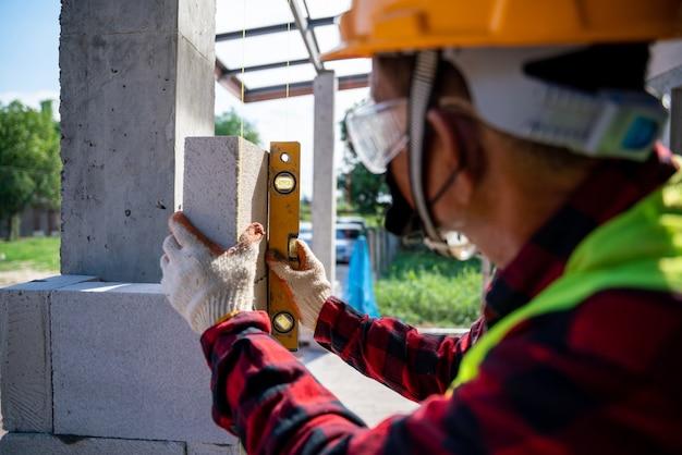 Primo piano del muratore che utilizza il livello dell'acqua, controlla l'inclinazione dei blocchi di cemento cellulare autoclavato. muratura, installazione di mattoni in cantiere