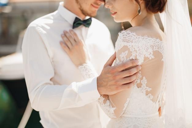 La sposa e lo sposo del primo piano stanno abbracciando teneramente