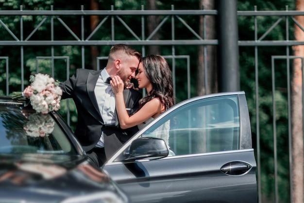 Chiudere la sposa e lo sposo in piedi vicino alla macchina