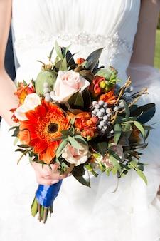 Chiuda in su delle mani della sposa che tengono il bellissimo bouquet da sposa autunno