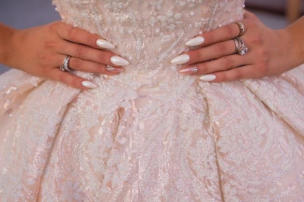 Abito da sposa in primo piano con un motivo splendidamente ricamato e mani in vita con una bella manicure.
