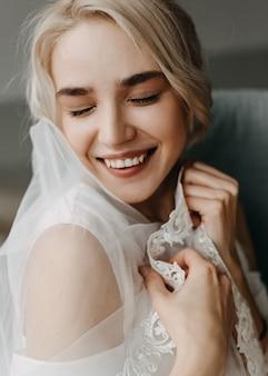 Primo piano di una sposa con i capelli biondi, sorridente.