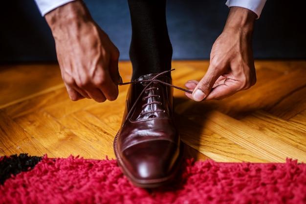 Primo piano di lacci di fissaggio sposo sulle sue scarpe.