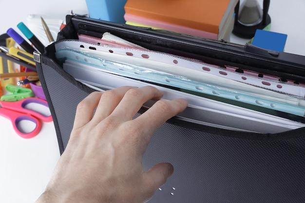 Avvicinamento. valigetta con cartelle di file e materiale scolastico su sfondo bianco