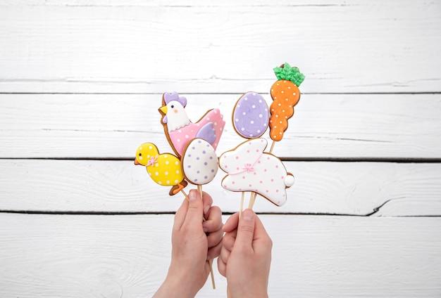 Chiuda su dei biscotti luminosi del pan di zenzero di pasqua sui bastoni. il concetto di arredamento per le vacanze di pasqua.