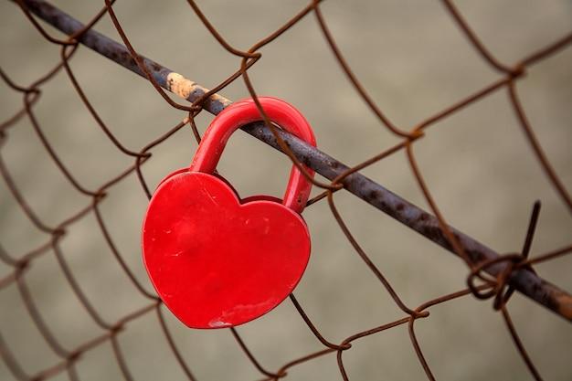 Primo piano di una serratura rossa brillante a forma di cuore su un ponte arrugginito