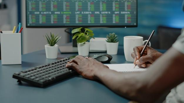 Primo piano del broker che scrive informazioni sul mercato azionario sul notebook