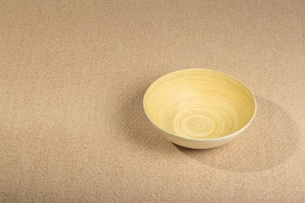 Primo piano sulla trama del tappeto marrone con ciotola di legno