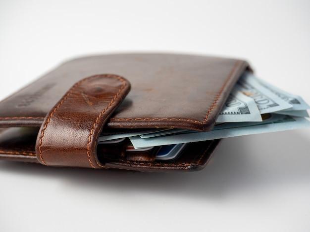 Primo piano di un portafoglio in pelle marrone farcito con banconote da un dollaro su sfondo bianco. il concetto di ricchezza, profitto, ricchezza