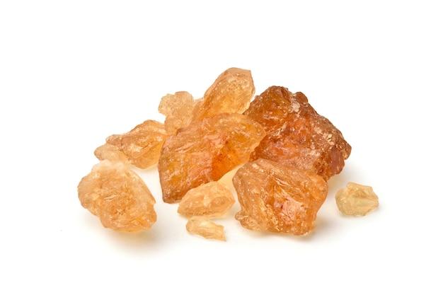 Close-up zucchero di roccia naturale marrone ottenuto dalla canna da zucchero su sfondo bianco.