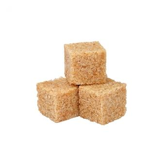 Close up cubetti di zucchero di canna isolati su bianco
