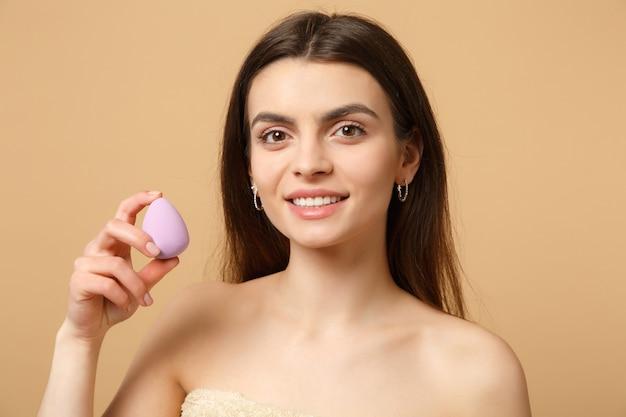 Chiuda in su donna mezza nuda bruna anni '20 con una pelle perfetta, trucco nudo isolato su parete pastello beige, ritratto. concetto di procedure cosmetiche sanitarie per la cura della pelle.