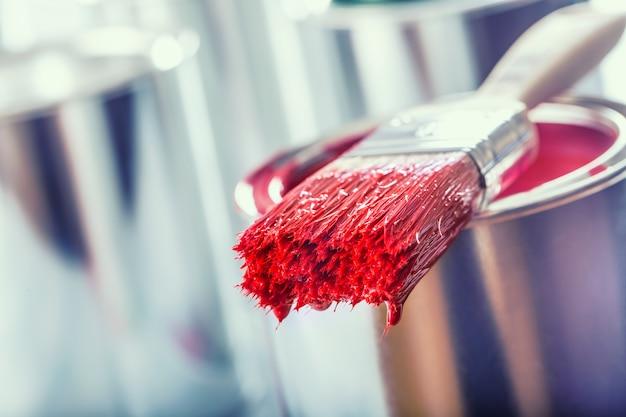 Pennello per primo piano con colore rosso sdraiato su un barattolo di vernice.