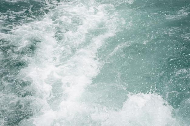 Primo piano onda di bolla colore turchese dal fondo della nave che rema nell'oceano per lo sfondo.